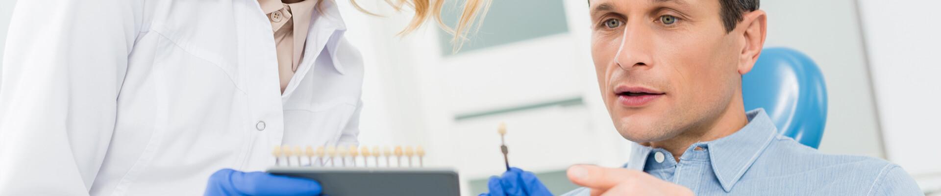 Patient examining dental prosthetic at dental clinic