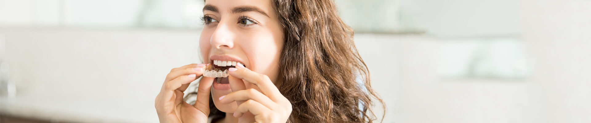 Closeup of beautiful young woman wearing clear aligner in dental clinic