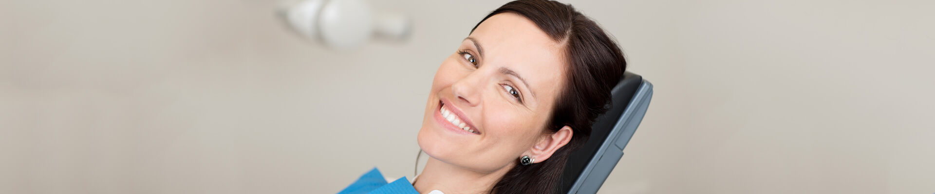Beautiful female patient at dentist office sitting on dental chair smiling